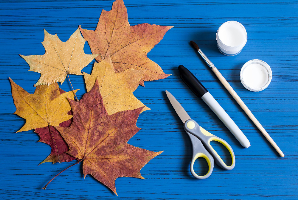 Collect fall leaves in different sizes. You will also need scissors, a marker, a paintbrush and white paint.