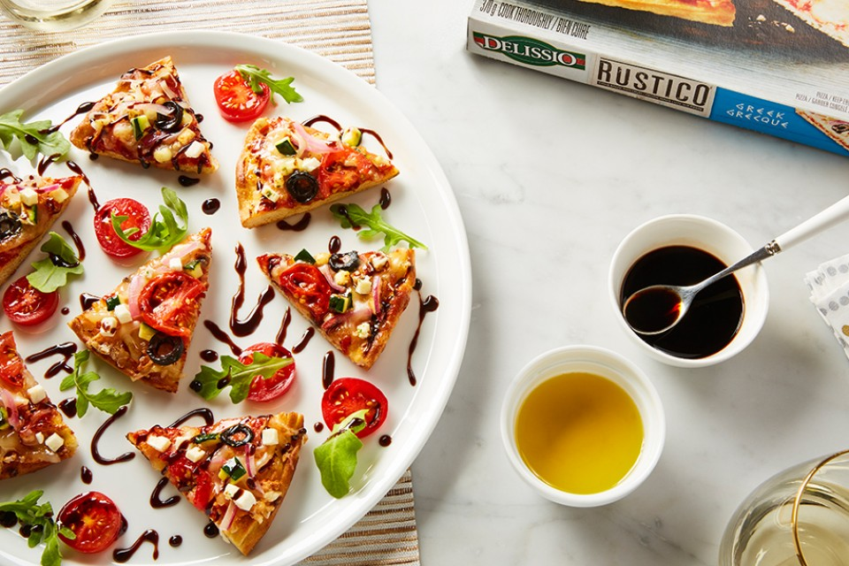 DELISSIO Greek Pizza Bites recipe. Combines balsamic drizzle, sliced tomatoes and a thin-crust Rustico Greek pizza.