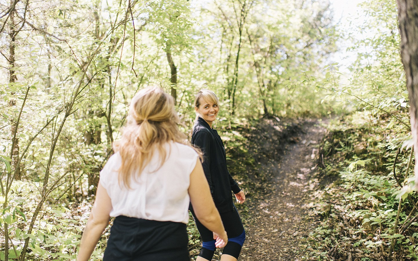 Two women walking through the forest together